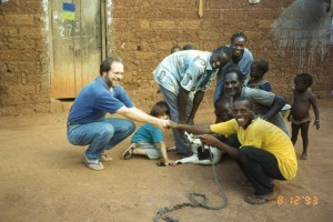 Guys slaughter goat, Philip and Kofi Ba grasp hands, Nathaniel holds goat leg, 8-12-93